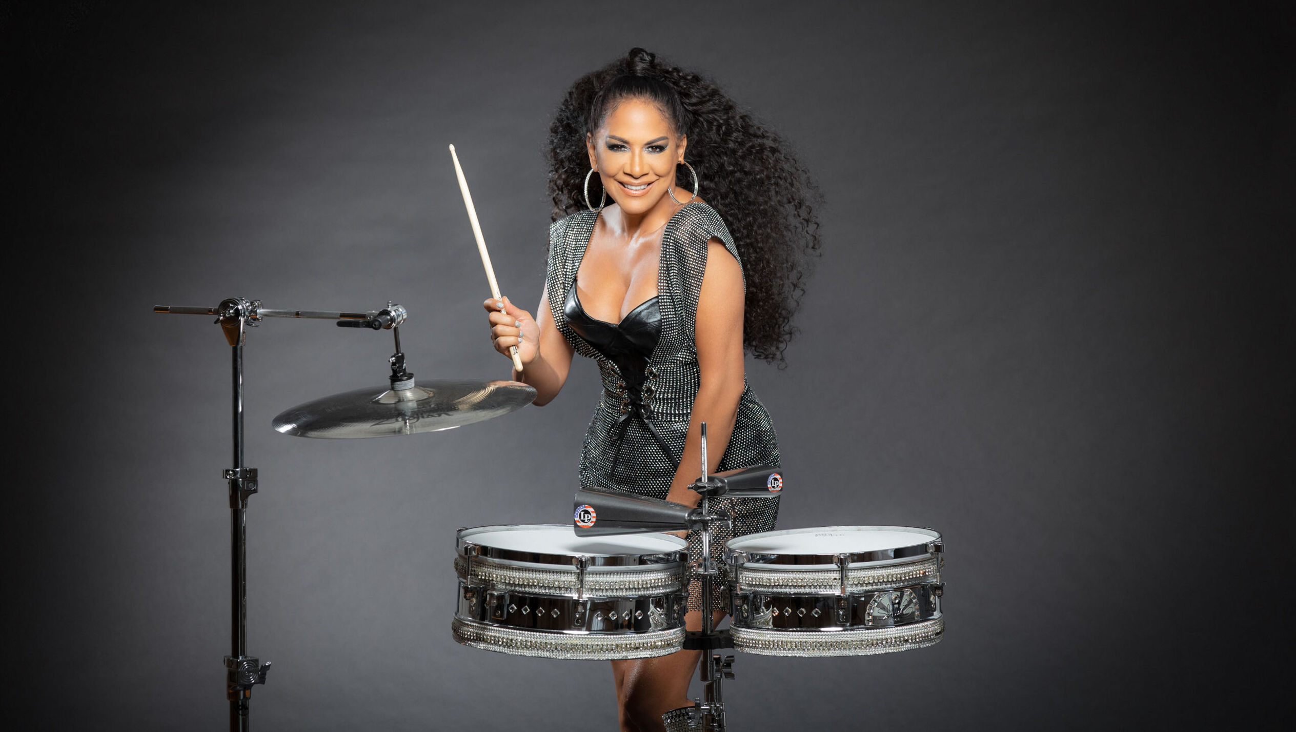 A woman with long black curly hair and tight dress stands in frot of a two-drum kit and cymbal set.