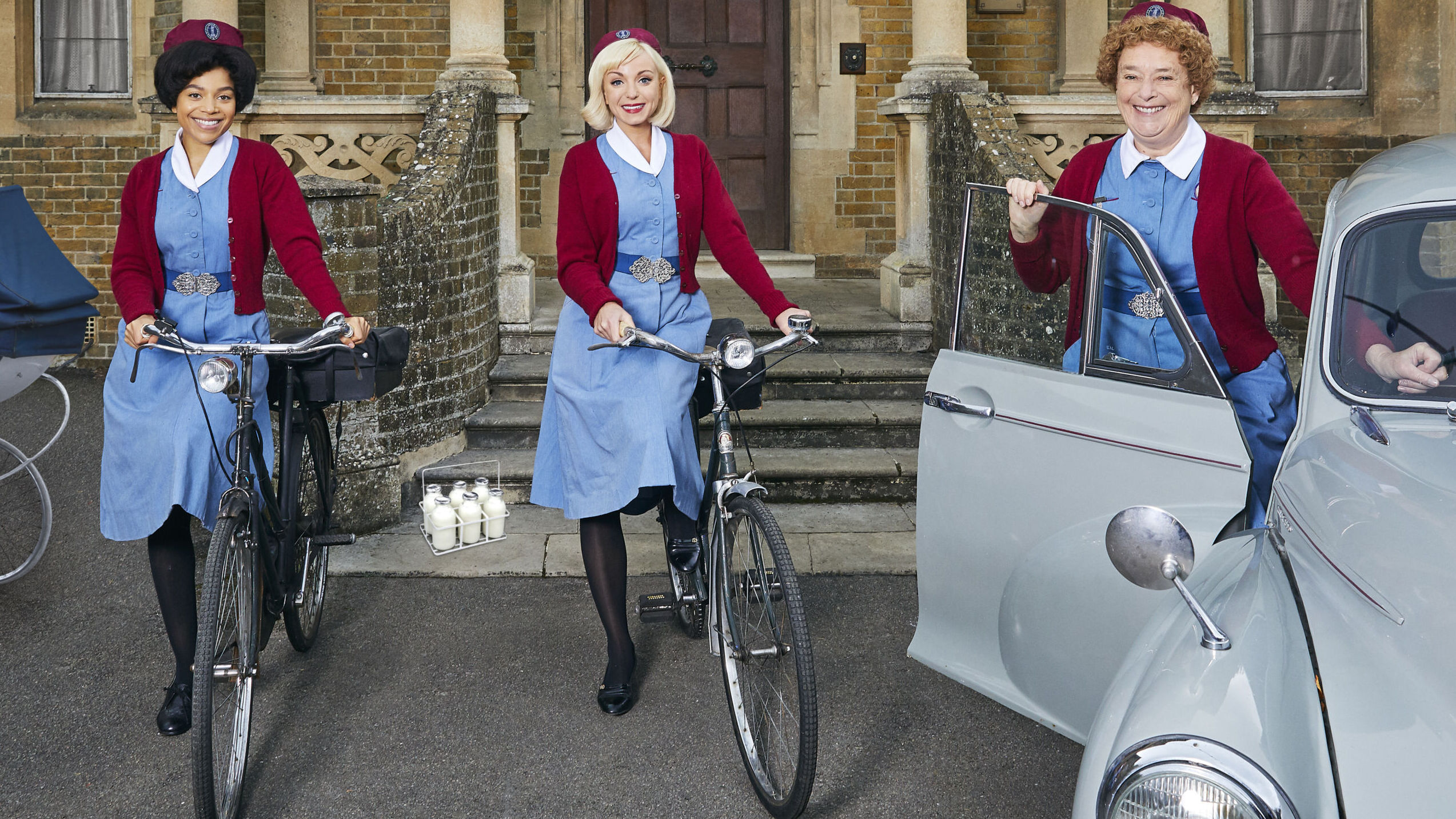 Three women are dressed in uniform of blue dress with maroon sweater and caps; two younger ones stand near bicycles; the older one behind a car door of a VW Beetle. They are in front of a large house.