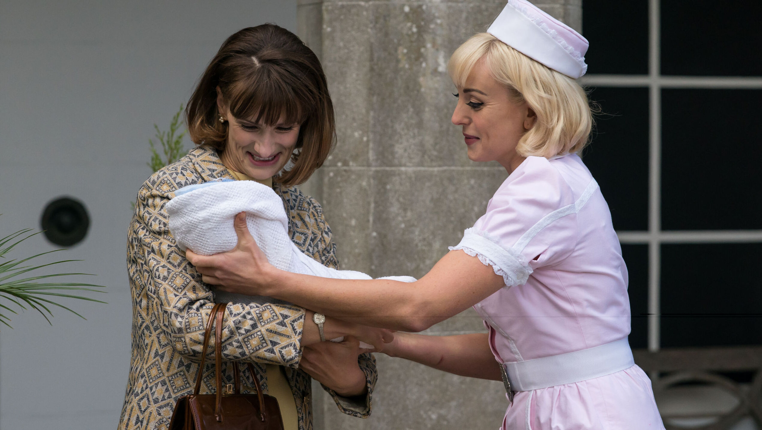 A woman with long dark hair accepts a baby wrapped in white fabric into her arms from a blond nurse in pink uniform.