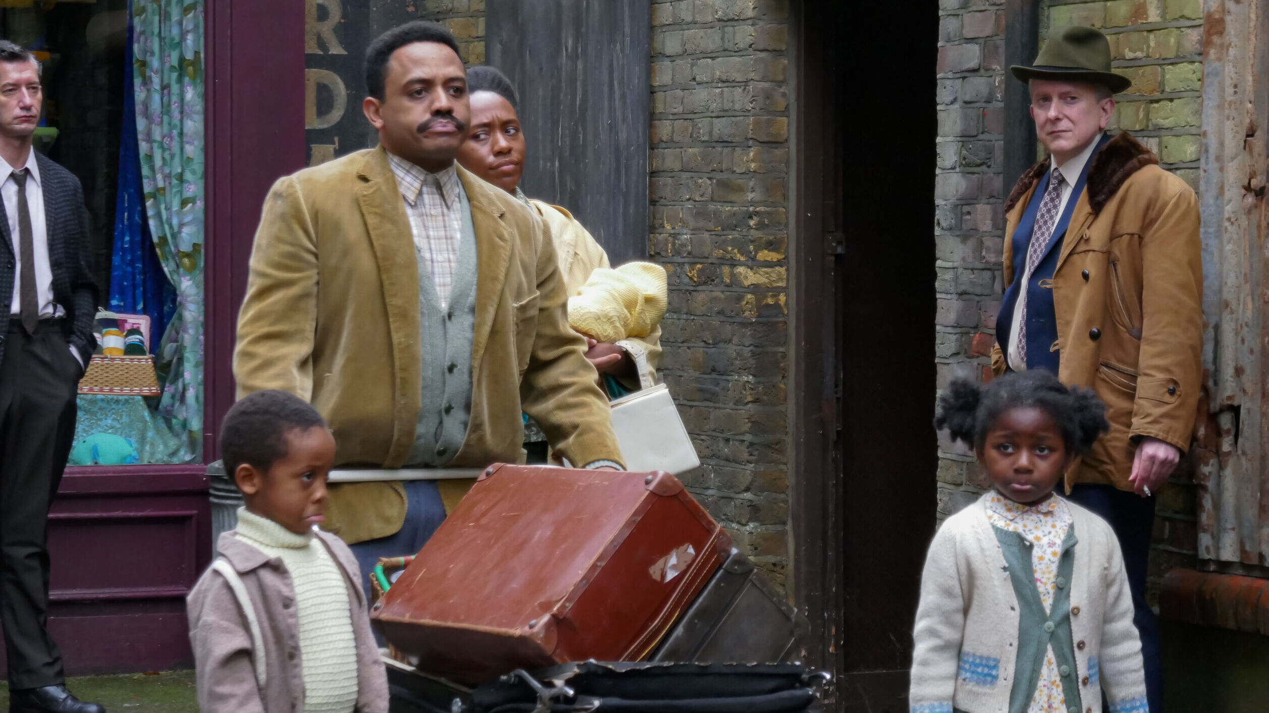A black man is in front of a woman, and two black children are a head of him on a drab street. A white man stands against a brick building.