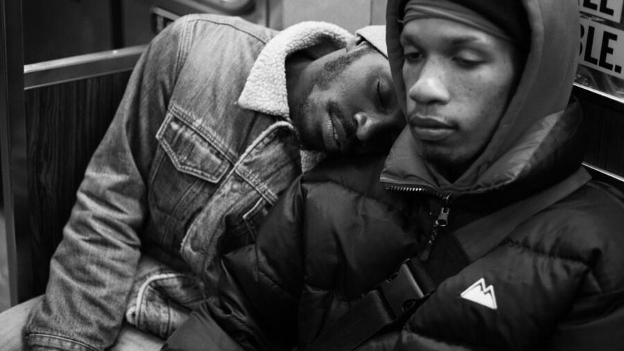 A black and white photo of two young black people dressed for cold weather on the subway. One leans his head on the others shoulder.