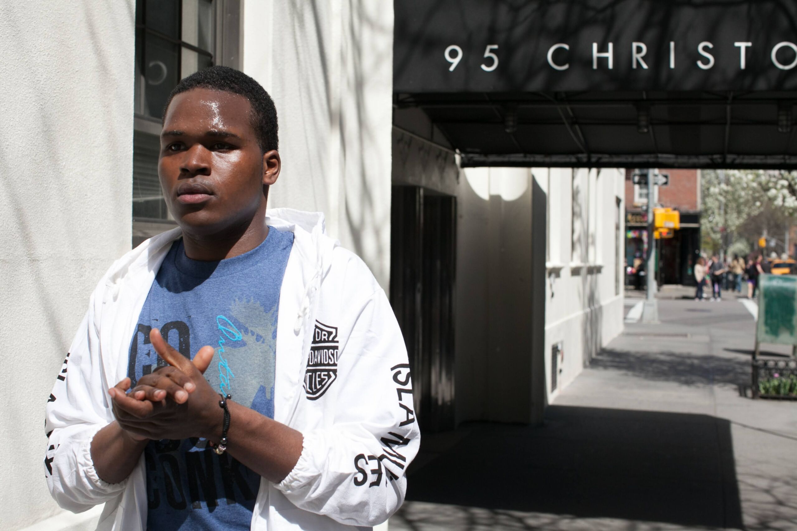 A Black youth in blue t-shirt and bright white zip hoodie walks past building awning that says 95 Christopher