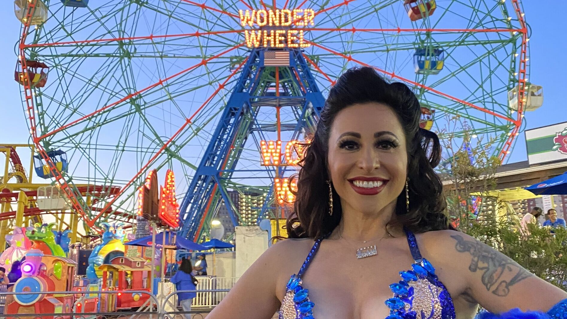 A woman with dress showing lots of cleavage, long blue gloves and feathered accessory stands in front of a ferris wheel