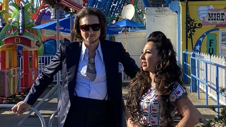 A man with white starch shirt unbuttoned over t-shit and wearing dark satin tuxedo jacked stands next to woman with 60s hair style and dress with face pattern. They are in amusement park i