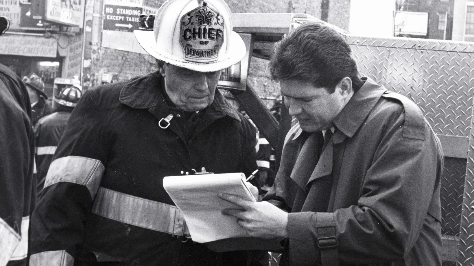 A fireman in chief helmet and fire jacket looks at notepad a man in trenchcoat holds between them on a street with hoses on it.