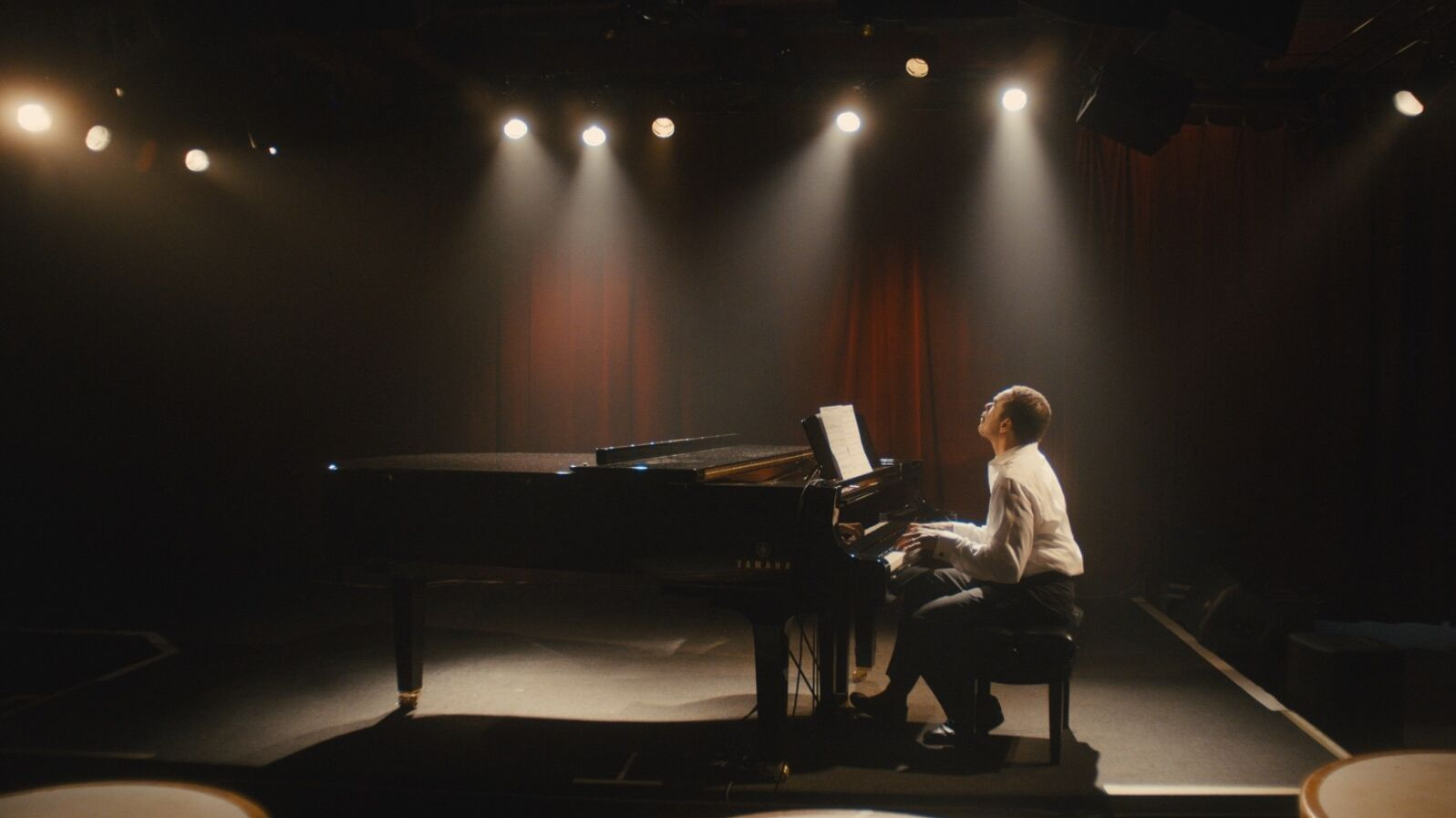 A black man plays a grand piano on a dramatically lit small stage with red curtains in background