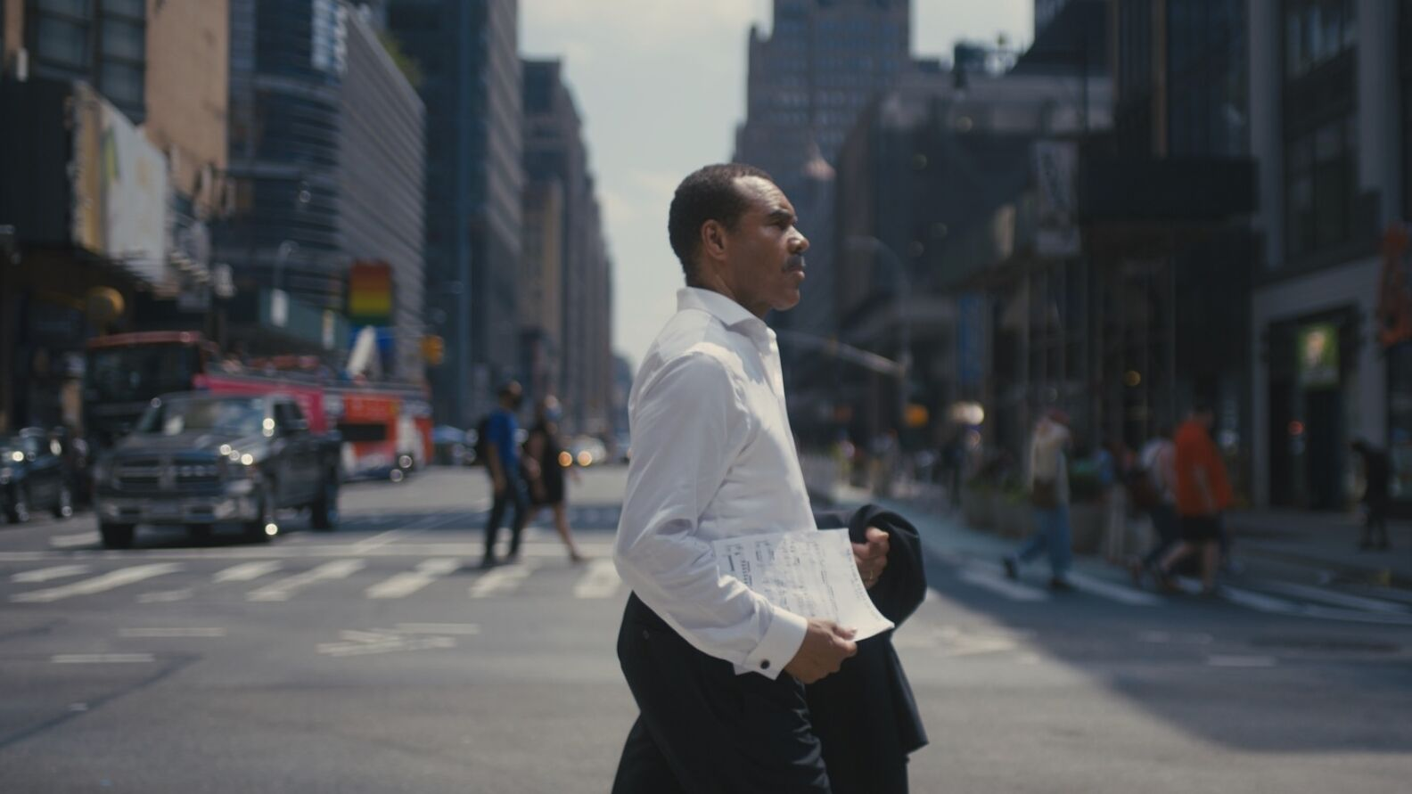 A ma in white shirt crosses avenue in New York City, holding a dark formal jacket and sheet music at his side.