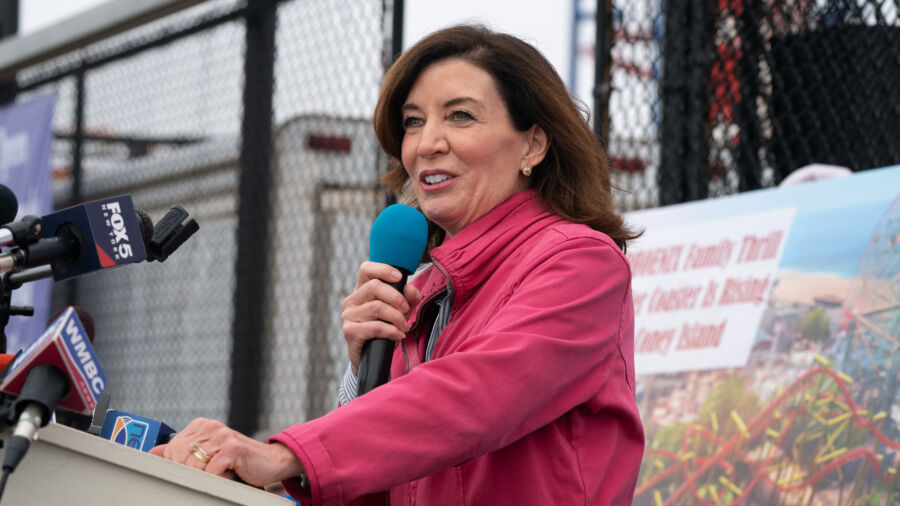 A woman with long dark hair in bright pink raincoat speaks into handheld microphone at podium in front of tall chainlink fence.