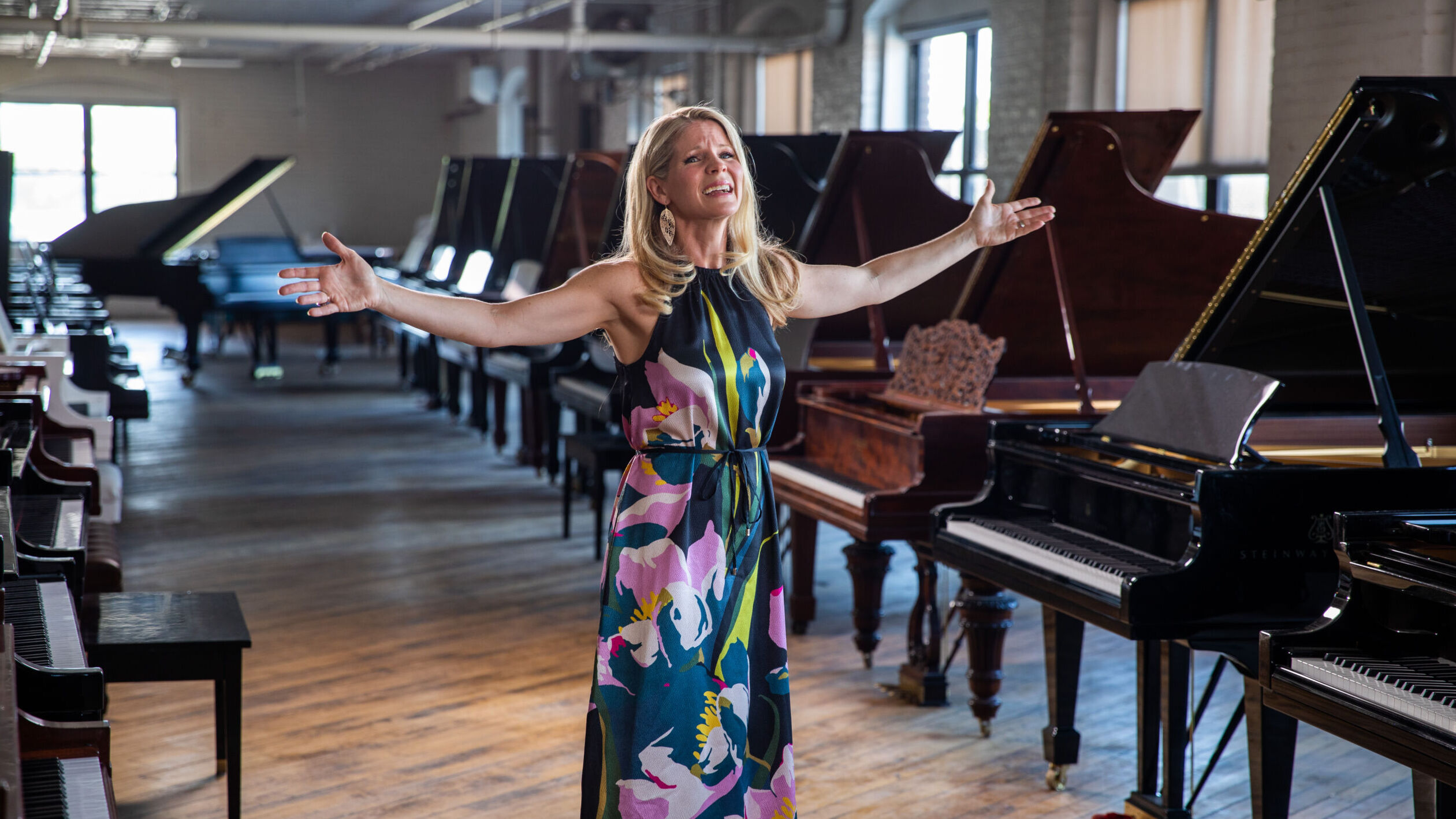 A blonde woman in flower patterned dress sings with outstretched arms in a loft space filled with grand pianos