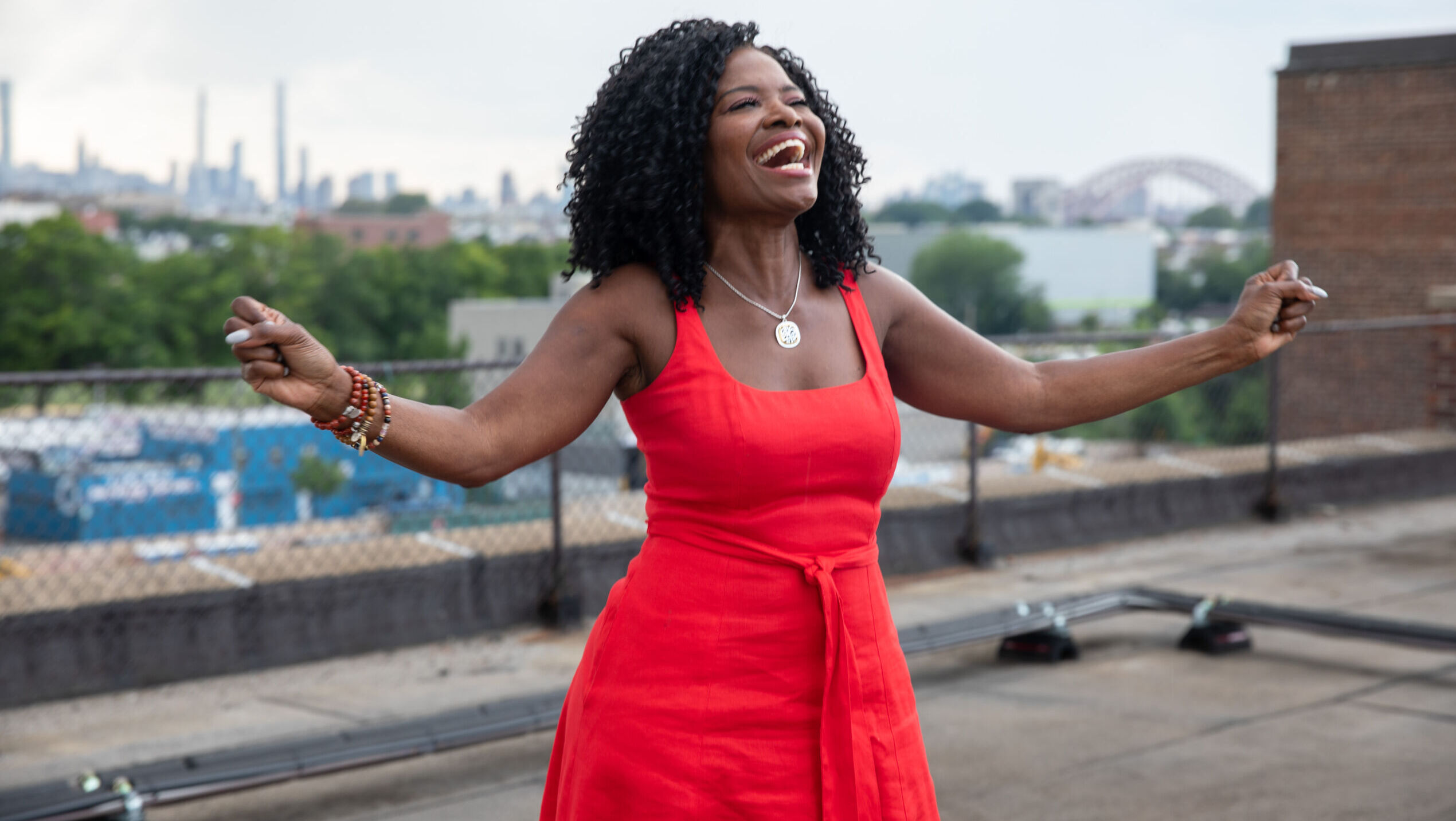 A black woman in red dress stands with outstretched arms on a rooftop with skyline in background