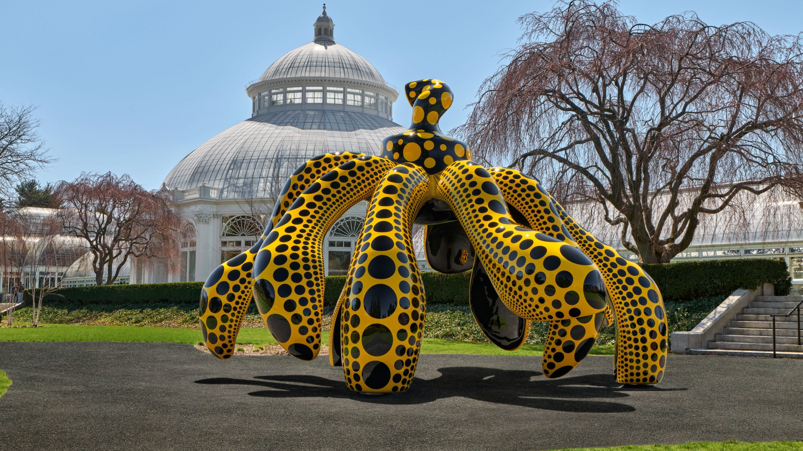 Image of the bright yellow and black dotted Dancing Pumpkin sculpture by Kusama