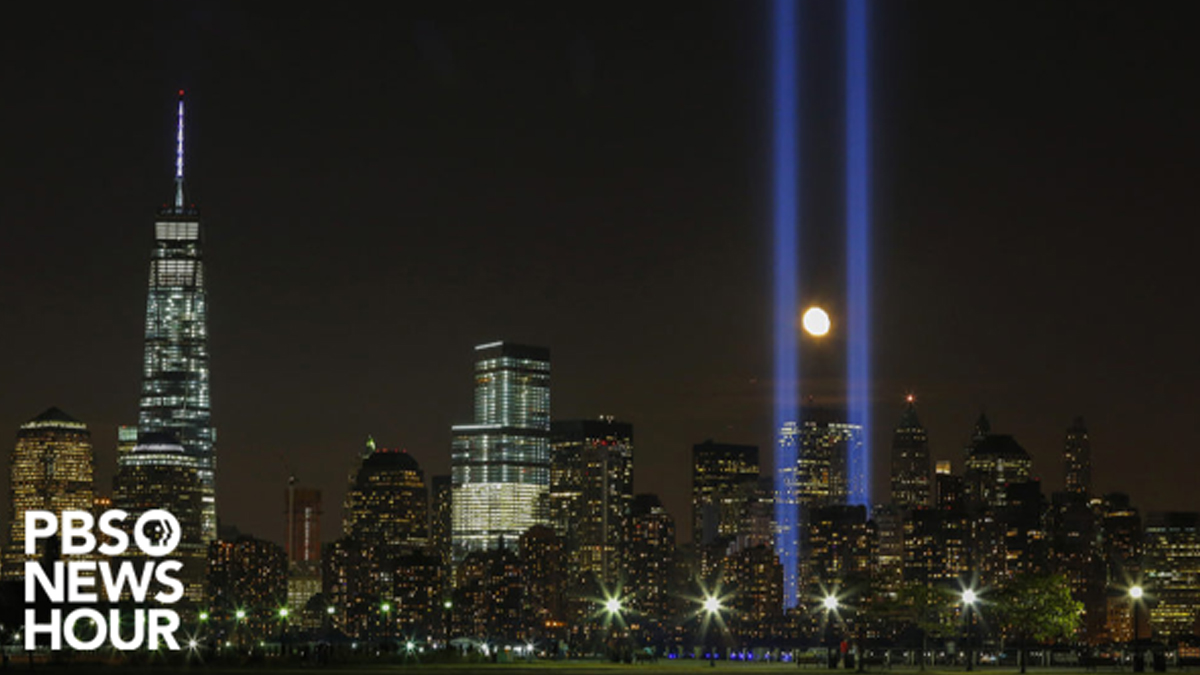 Two huge beams of light from the ground travel skyward in night scene of lower Manhattan