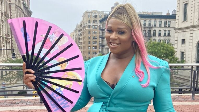 A woman in teal form-fitting two-piece suit holds a pink fan