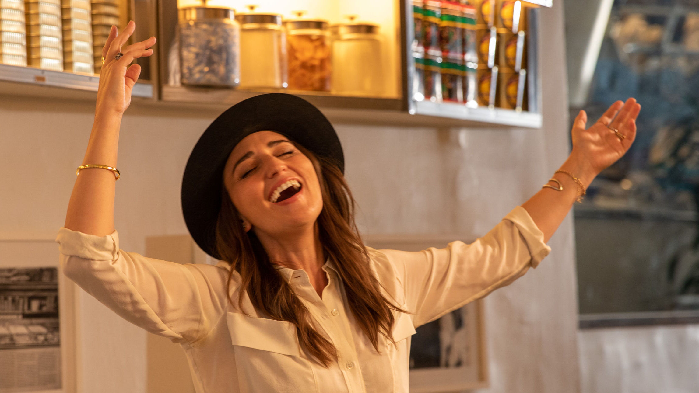 A woman in long white shirt, black pants and black-rimmed hat sings with outstretched arms in a shop that has lit display cases high on the wall.