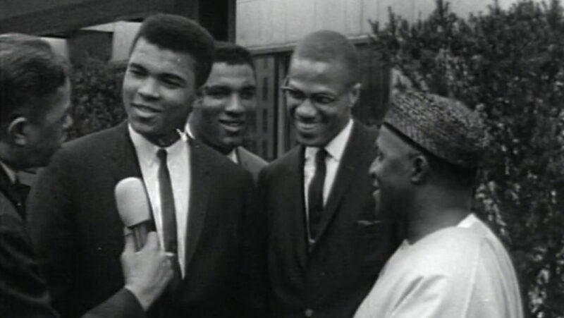 A white hand holds a microphone and a Black man in dark suit and tie looks smiling in the direction of it; next to him are smiling Black men, two in suit and ties and one in African formal clothing