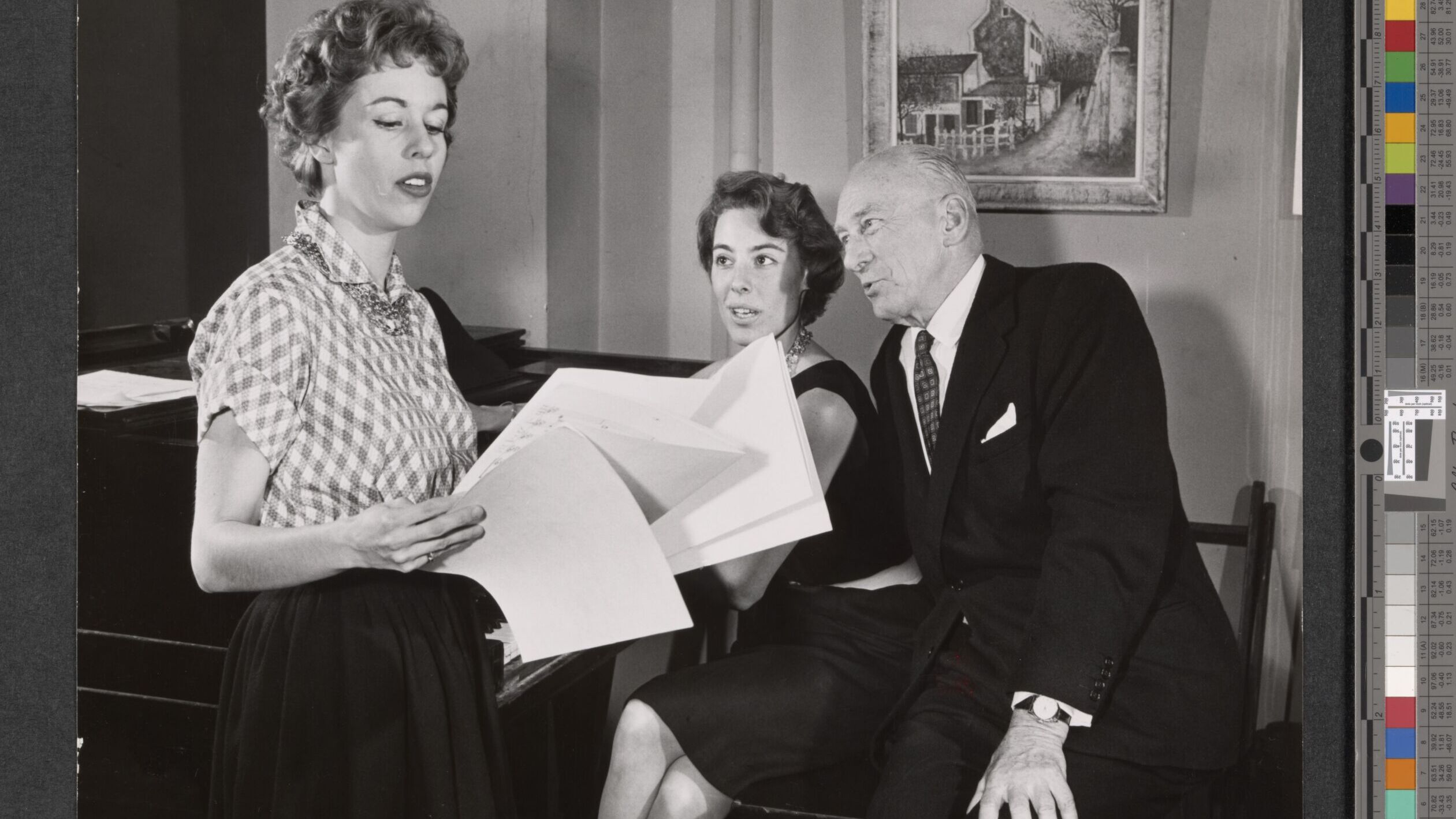 Black and white photo of two women and one man in suit, reading or singing from papers in rehearsal.
