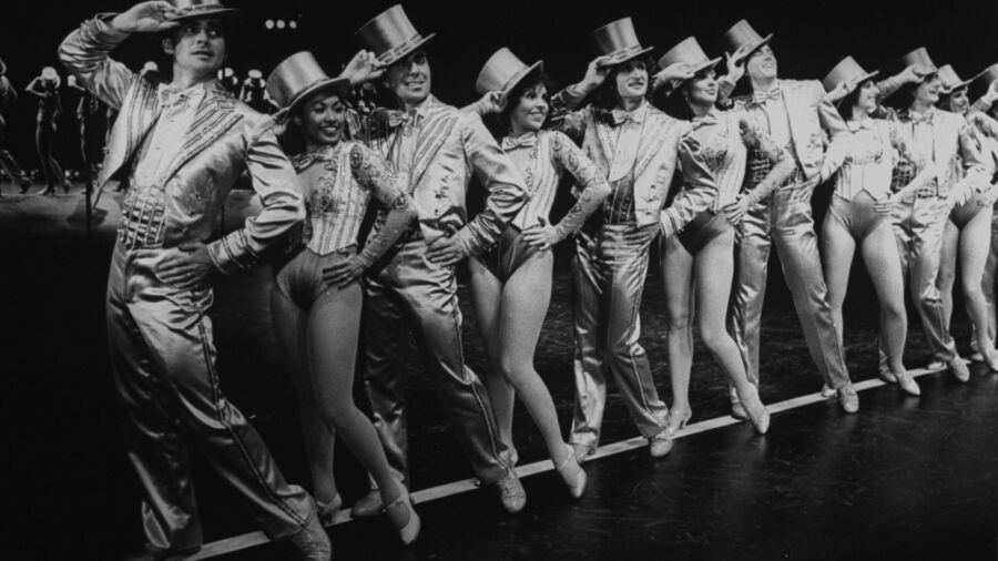 A black and white photo of men in women in stylized suits and top hats posing in a line on stage