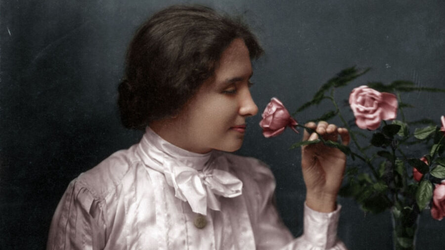 A woman in pale pink blouse with high collar and bow sits next to a thin vase with roses. She holds a stem gently in her left hand and directs the pink rose bud towards her nose. She smiles faintly.