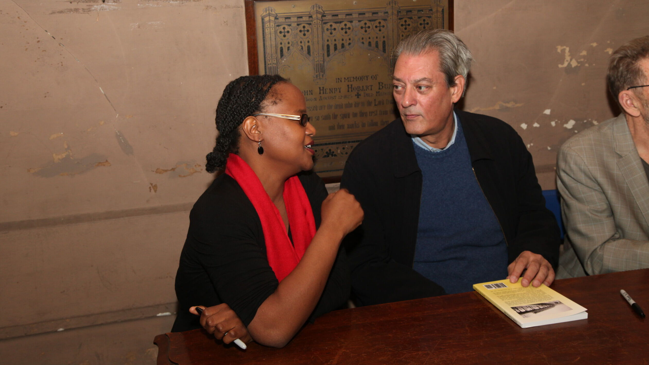 A black woman holds a pen and talks to white man who listens next to her. Both are seated at wooden table. There is a book on table in front of man. Behind them is a commemorative plaque on a wall that needs repainting.