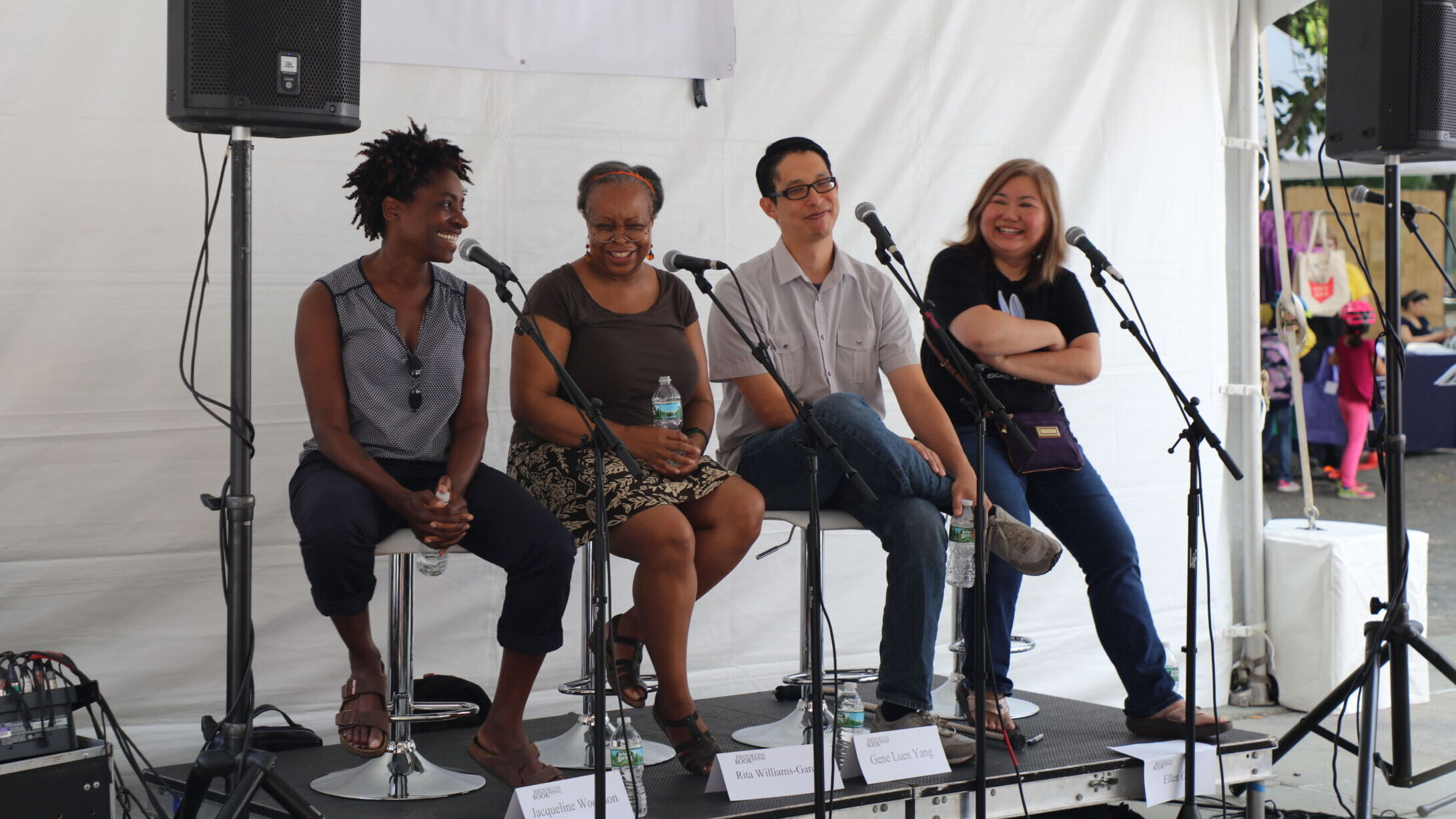 Four adults in casual dress sit on stools on a raised platform with white tent backdrop. Each has a standup microphone in front of their seat. They are all smiling as if sharing a laugh.