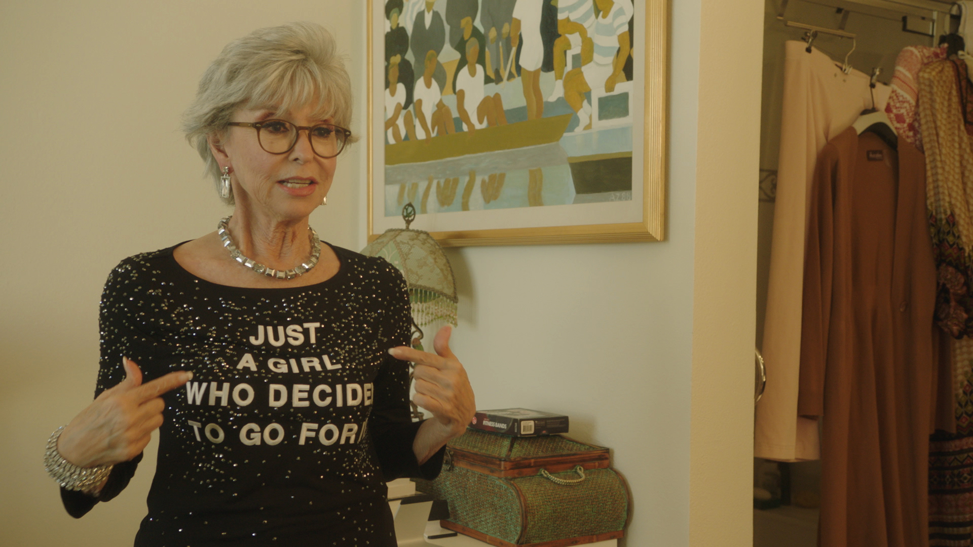 A woman with short white hair, eyeglasses points to her t-shirt. She stands in a room in a house with a painting on wall.