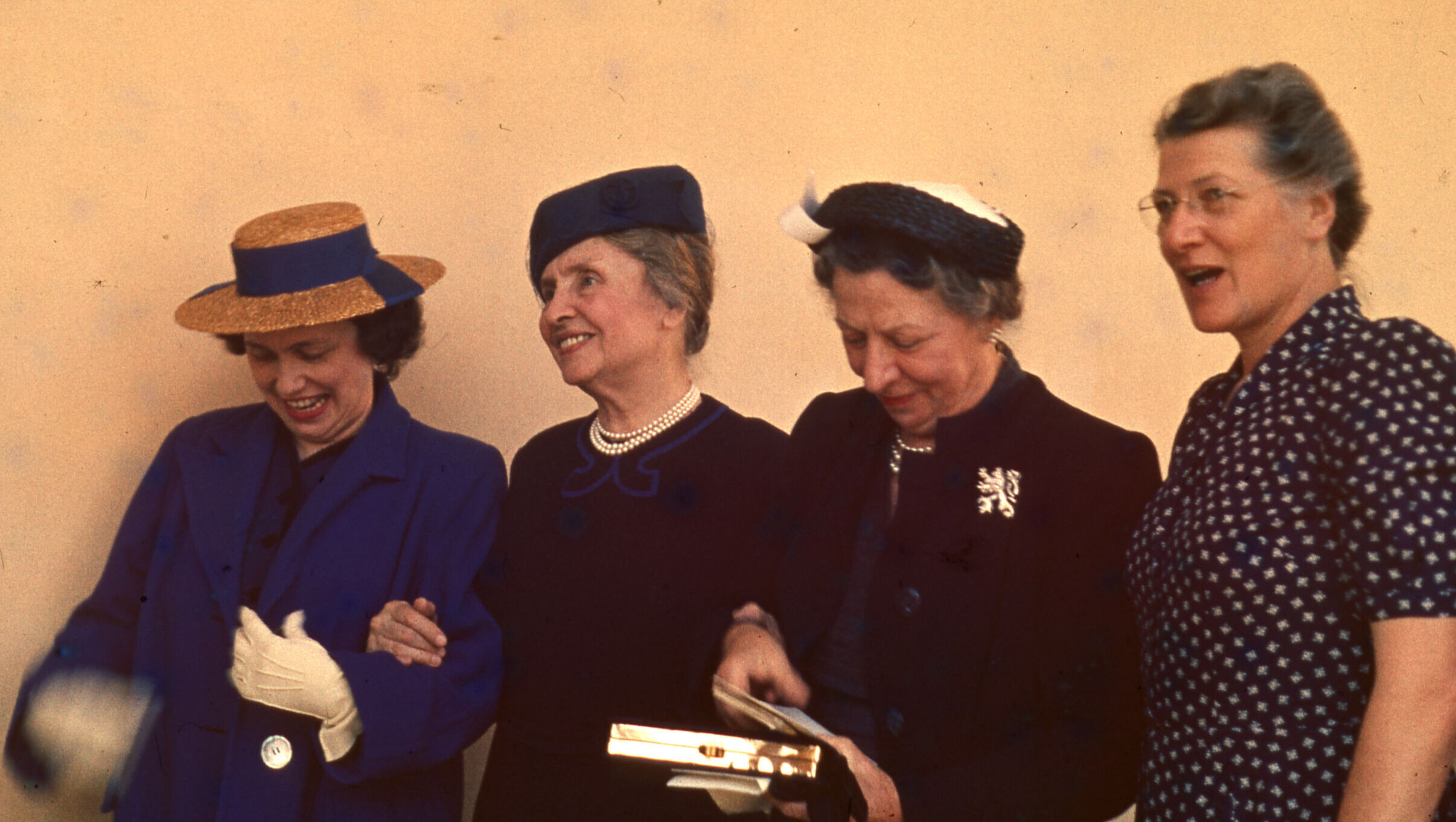 Four women stand side by side, three with linked arms. Three wear hats and formal dress; the one on far right does not have hat and appears more casually dressed.