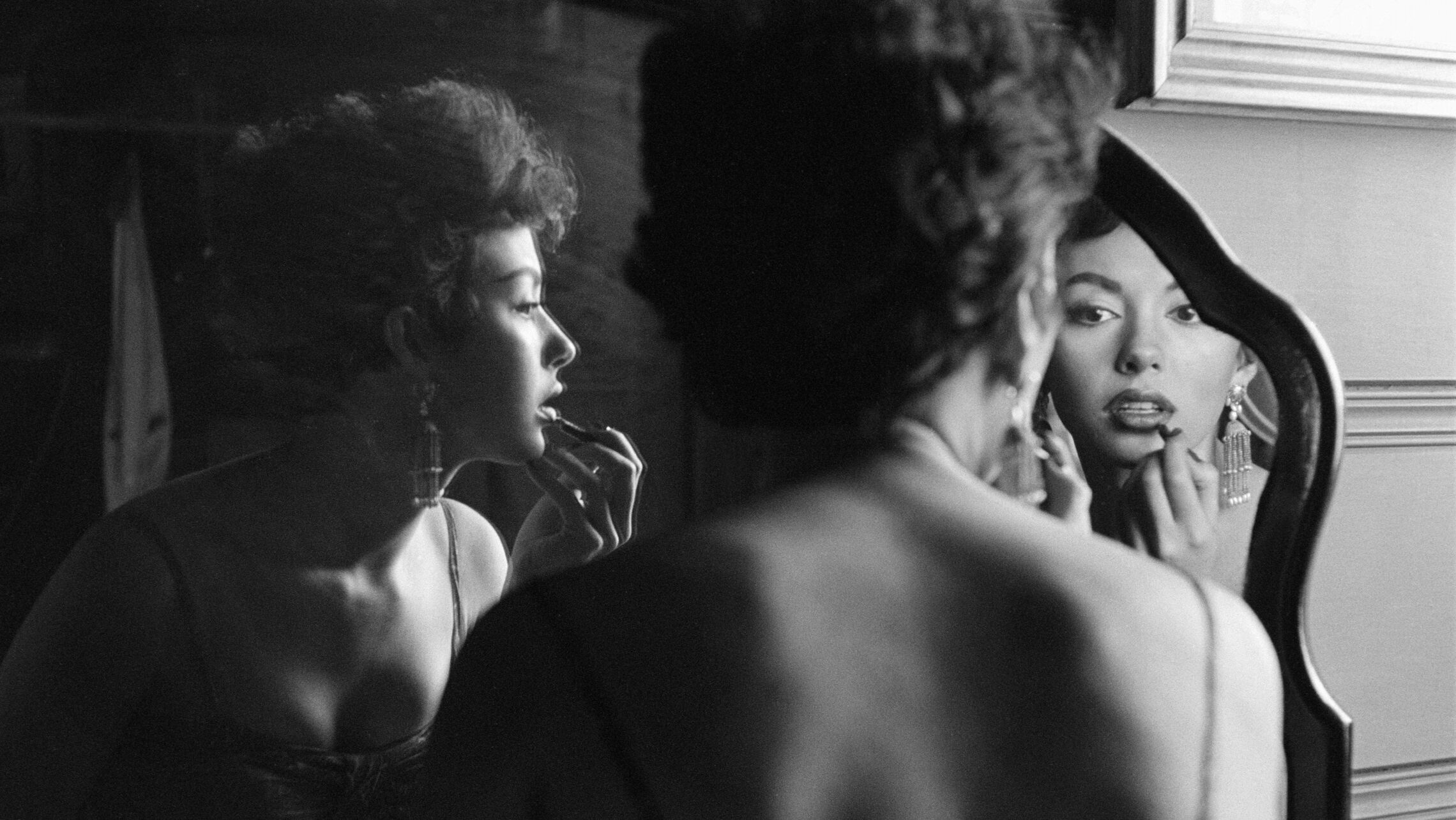 A woman in slip negligee is photographed from behind as she looks in folding mirror, applying lipstick.
