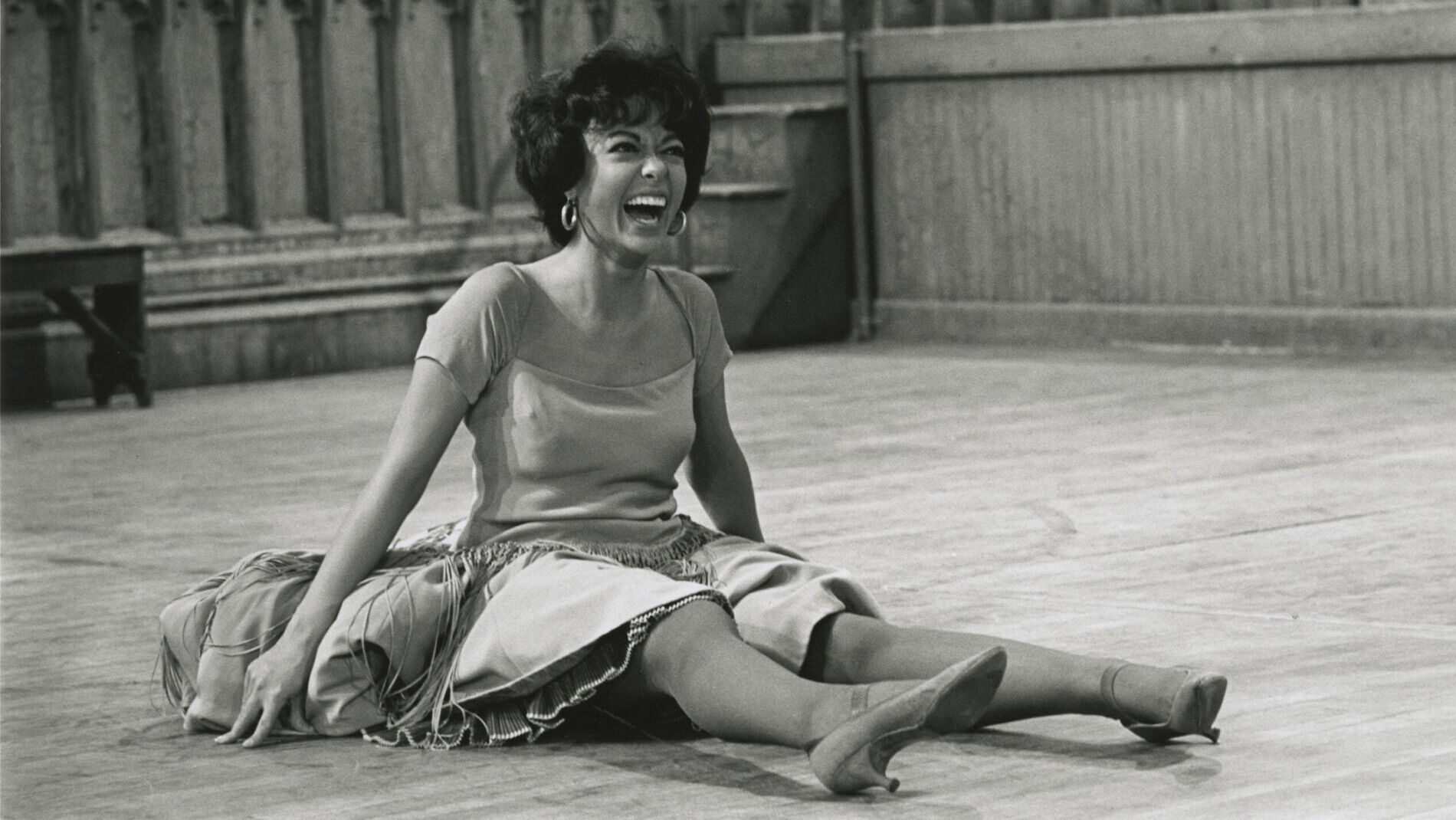 A woman with dark hair and wearing dress sits on floor with her legs stretched in front of her. She is laughing.