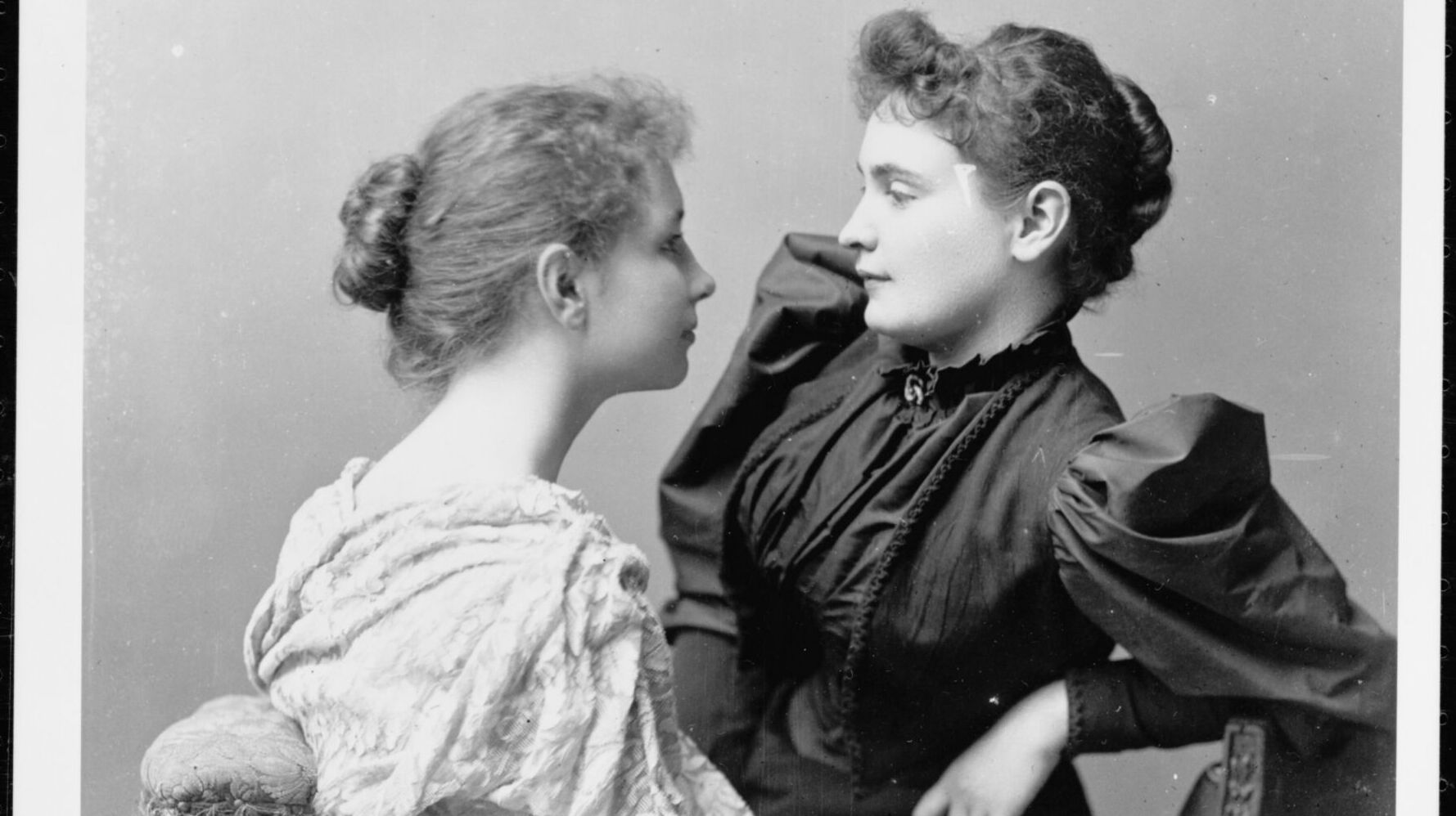 Two young women face each other while sitting on a bench. They both have hair loosely swept into bun and curly bangs. To right, the taller woman wears a formal dark gown with puffy sleeves. The other woman wears a loose fitting light-color top.