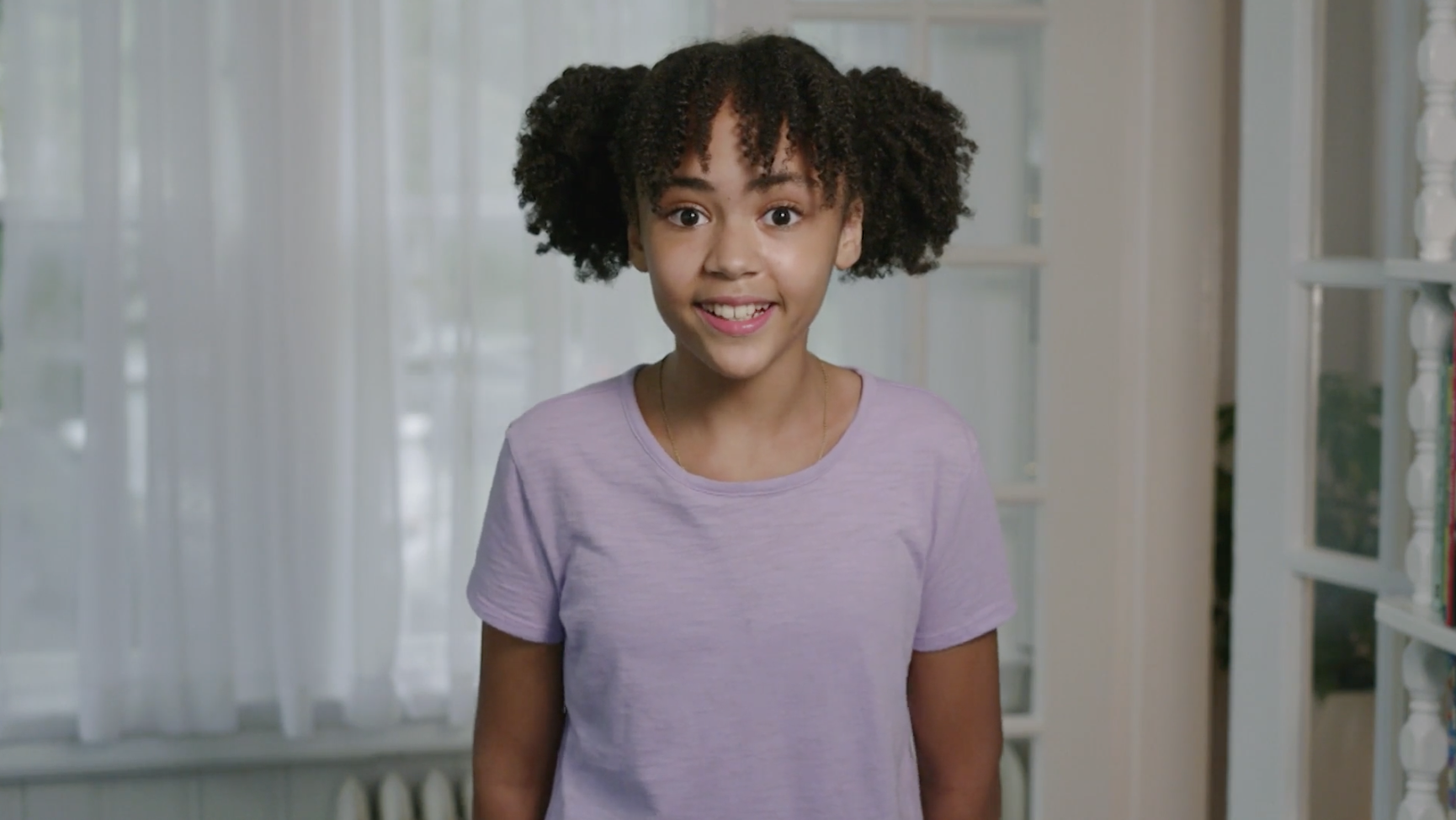 A young Black girl, shown from the waist up, smiles at the camera. She has bangs and two big, curly pigtails on either side of her head. She is wearing a lavender t-shirt and is standing in front of a window with sheer white curtains.