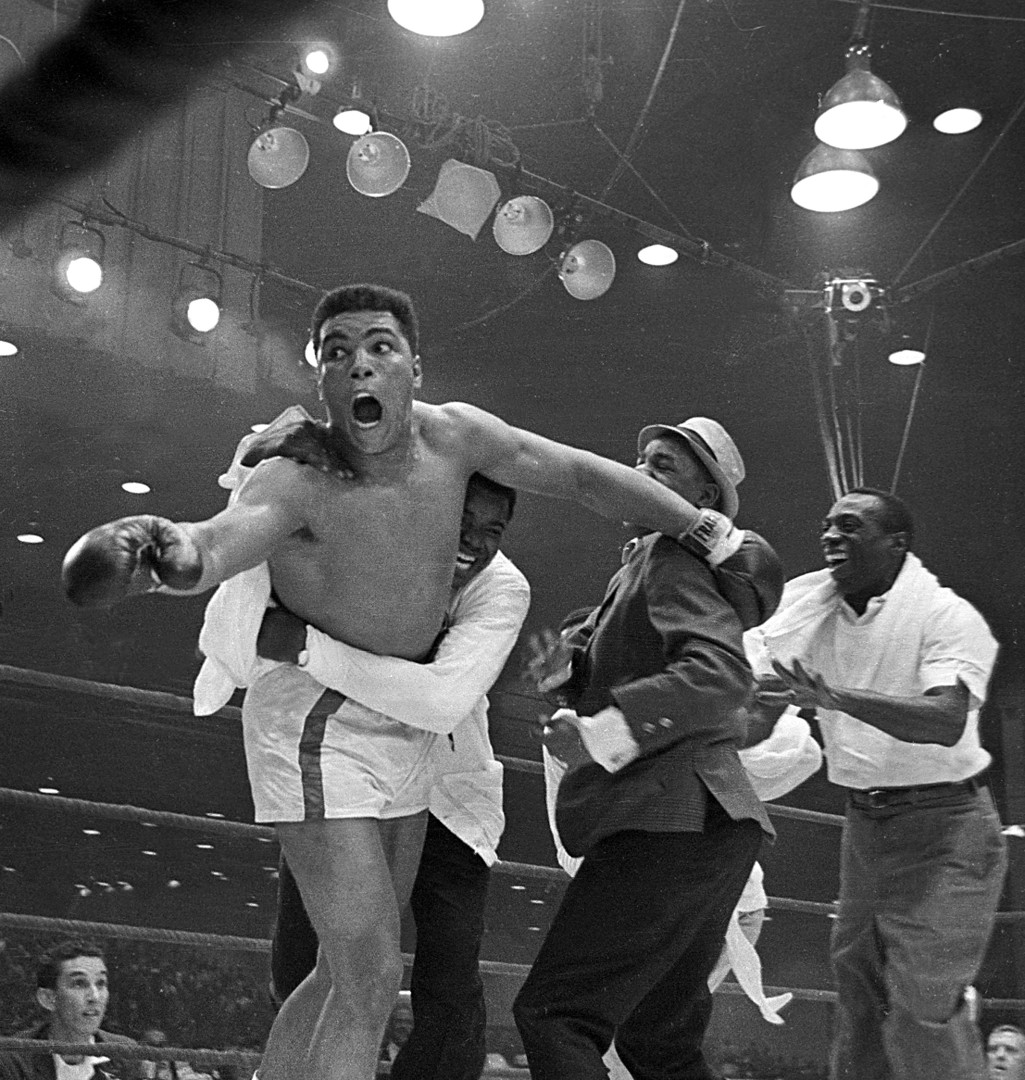 A black man in boxing shorts lunges towards camera with outstretched hands while person in white hugs his waist and others rush towards him, smiling.