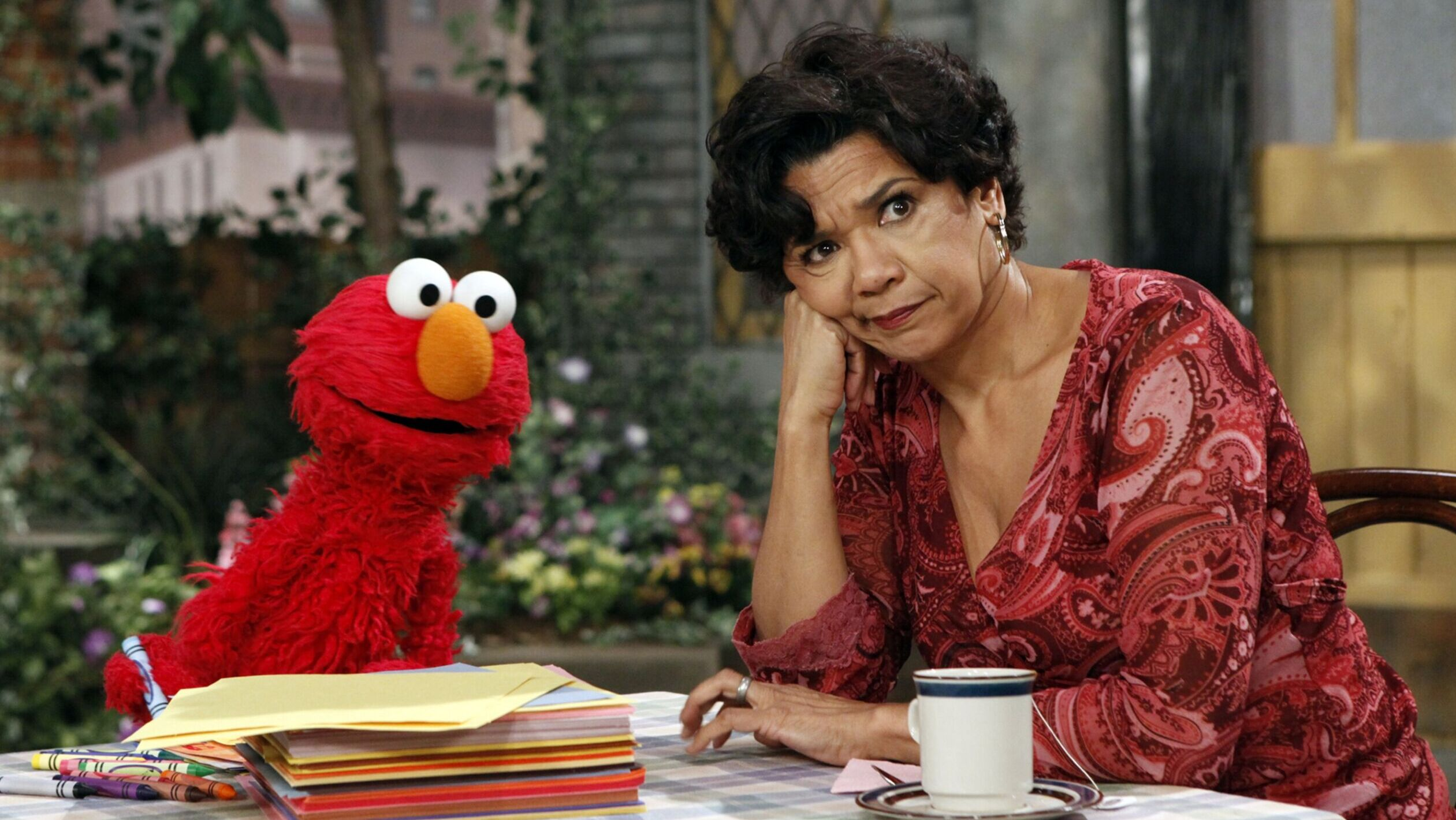 A red puppet character with large orange nose and big round eyes at top of his head sits at a table with a woman in red dress who leas the side of her face on her fist. There is a coffee cup in front of her and books in front of the puppet. The woman looks like she doesn't like something
