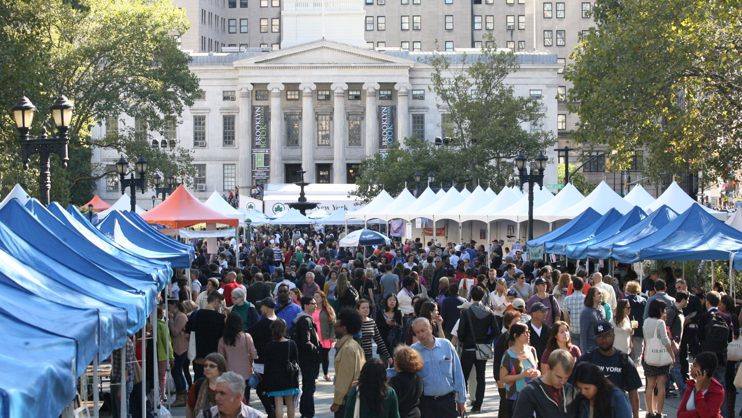 A crowd of people between rows of blue canopy tents. In the background is a white building with columns and peaks of white tents.