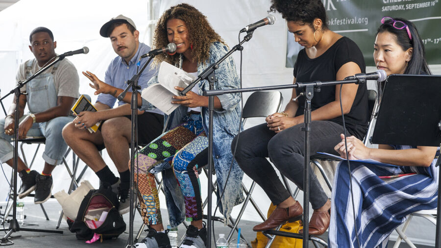 Five people in casual dress sit on tall chairs on outdoor stage. Woman in center with thick curly hair reads from a book into a standing microphone, and holds her hand outstretched. The other people listen attentively.